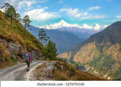 Male tourist backpacker walk through scenic mountain road with view of Himalaya range near Binsar Uttarakhand India.
