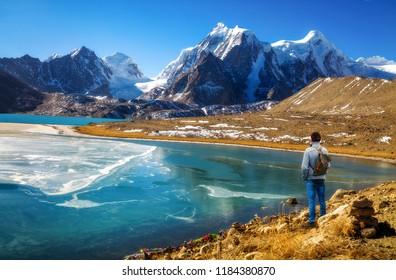 Male tourist enjoy scenic view of high altitude Gurudongmar lake at North Sikkim, India