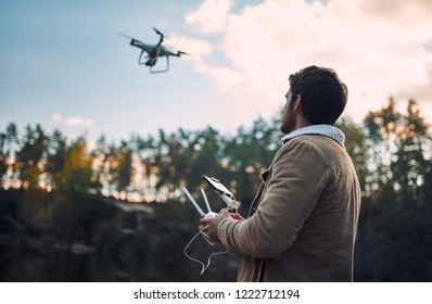 Male tourist exploring new places. Handsome bearded man on nature with quadcopter. Using drone while standing near lake.