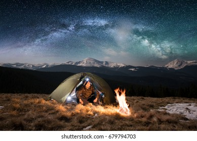 Male tourist have a rest in his camping in the mountains at night. Man with a headlamp sitting near campfire and tent under beautiful night sky full of stars and milky way, and enjoying night scene