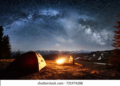 Male tourist have a rest in his camp near the forest at night. Man sitting near campfire and tent under beautiful night sky full of stars and milky way. Long exposure