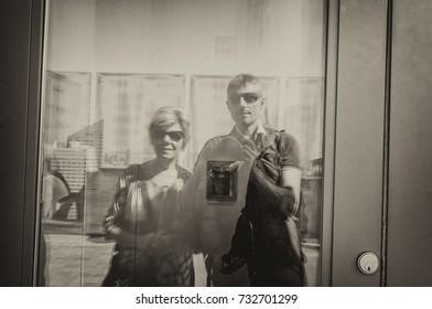 Male tourist with his mother taking selfie on the buildings glass mirror.