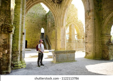 Male tourist in Jerpoint Abbey, a ruined Cistercian abbey, founded in the second half of the 12th century, located near Thomastown, County Kilkenny, Ireland.