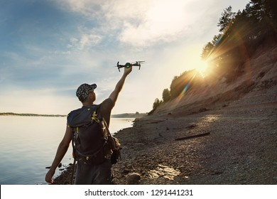 Male tourist launching drone from hand in beautiful sunset in woodland.