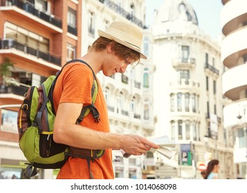 male tourist looking map on a street of european city, man traveler with backpack in Valencia