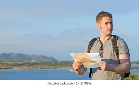 Male tourist with map on vacation.