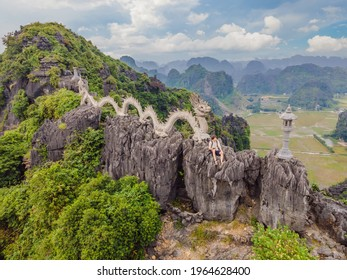 Male tourist on the background of Amazing huge dragon statue at limestone mountain top near Hang Mua view point at foggy morning. Popular tourist attraction at Tam Coc, Ninh Binh. Vietnam travel