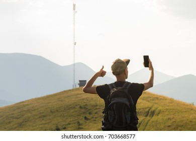 Male tourist on hiking trip happy to receive mobile network connection. Young man on vacation in mountains lifts thumb up and holds cell phone near the cell network tower