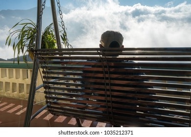 Male tourist sit on swing seeing mountain landscape with low white clouds under brilliant sky. Ideas for travel and feeling.