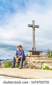 A male tourist sits resting next to Summit cross on Zwoelferhorn Mountain, Sankt Gilgen in Salzkammergut region, Austria