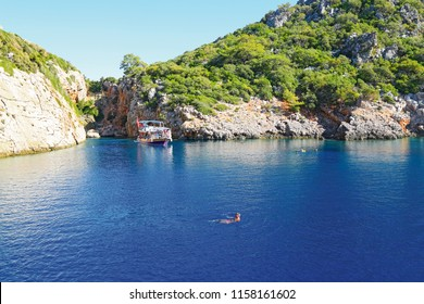 A male tourist swimming in deep blue waters of magnificent of Korsan Cove. View of the rocky Mediterranean coast.  September 2017, Adrasan   Antalya-Turkey