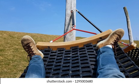 Male tourist swinging in hammock, lazy free time, refreshment on peaceful meadow