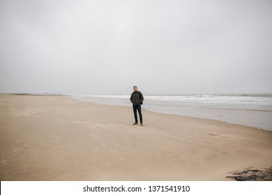 Male tourist walkin along the North Sea. Man with backpack stand on the coast in rainy weather. Beautiful sea