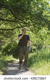Male tourist walking in forest on trail and speak by cellphone