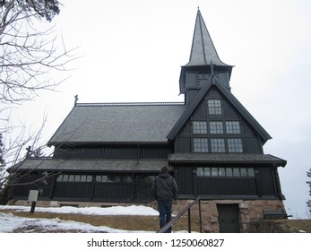 Male tourist walking toward a dark wooden church in Holmenkollen district in Oslo - Norway