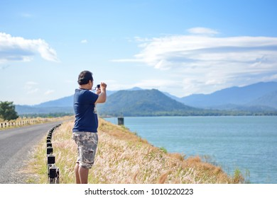 Male tourists are photographing a lake that is a natural attraction. Concept for Travel. Selective focus.