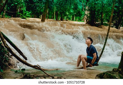 Male tourists sit on a vine swing at Tad Sae waterfalls. A trip to the Tad Sae waterfalls Luang Prabang, Laos.