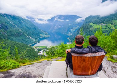 Male tourists sitting on the Queen Sony Chair at the Flydalsjuvet Viewpoint. The summer landscape of Geiranger small village which is located at the end of the Geirangerfjord. Norway.
