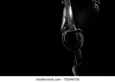 male in in tradition kendo armor with Samurai sword katana. shot in studio. isolated on black background (black and white)