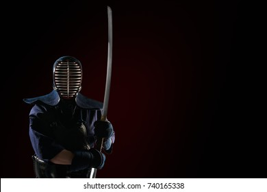 male in in tradition kendo armor with Samurai sword katana. shot in studio. isolated on black and red background