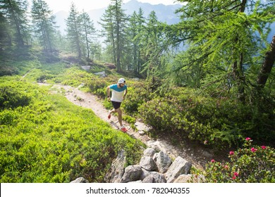A male trail runner running along a trail in the mountains, through a green landscape with trees and plants in spring.