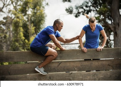 Male trainer assisting woman to climb a wooden wall during obstacle course