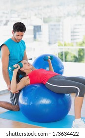 Male trainer helping woman with her exercises at a bright gym