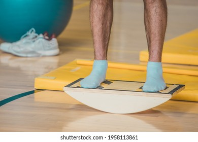 Male trainer seen using a wooden balance board. Different balance sports equipment is seen around in a gym indoors.