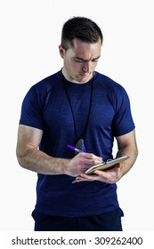 Male trainer writing on his clipboard on a white background