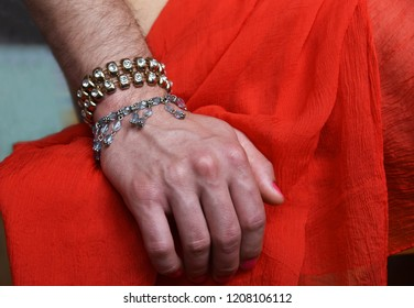 Male transvestite hairy hand with golden bracelet and nail polish on nails