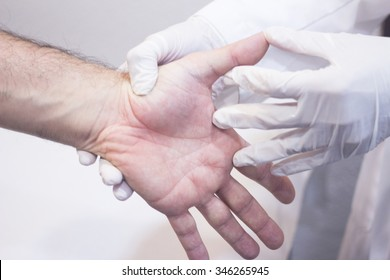 Male Traumatologist orthopedics surgeon doctor examining middle aged man patient to determine injury, pain, mobility and to diagnose medical treatment in hand fingers and wrist.
