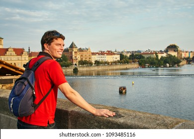 male traveler with backpack on the Charles Bridge on Vltava River embankment. Prague, Czech Republic