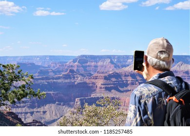 A male traveler with backpack taking the photo with smartphone of beautiful view at south rim of Grand Canyon National Park, Summer in Arizona USA.