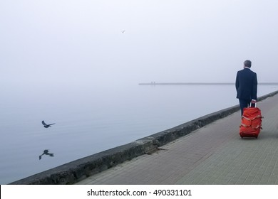 Male traveler carrying vibrant red suitcase by the shore of Curonian lagoon in Nida, Lithuania