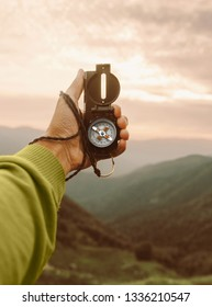 Male traveler explorer searching direction with compass in summer mountains, point of view.