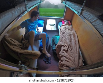 Male traveler gets up from his bed while his girlfriend rests during a scenic train ride through the scenic countryside in Vietnam. Young tourist couple taking the sleeper train to travel across Asia.