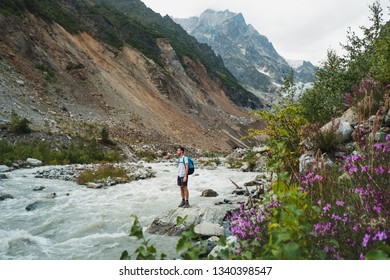 male traveler looking at flashy stream flowing in mountain valley