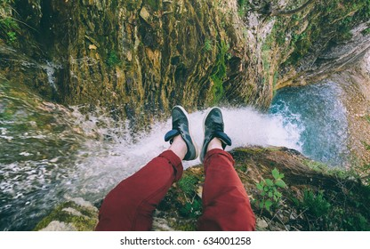 Male Traveler sitting on cliff with waterfall view, Point Of View Shot. Travel Lifestyle adventure vacations concept