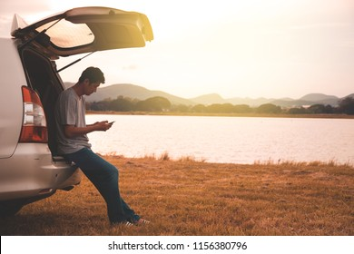 Male traveler sitting on hatchback car with mountain background in vintage tone