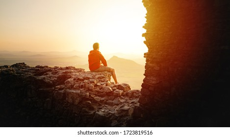 Male traveler sitting on high rock cliff spending time for recreating in nature environment, hipster guy enjoying sunrise during. Discovery, Travel, Adventure