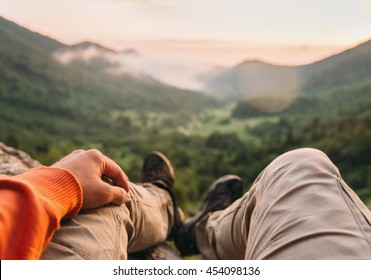 Male traveler sitting in summer mountains at sunset, point of view shot