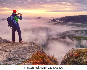 Male traveler using mobile cell phone sharing fall mountains landscape view for friend through scial network.