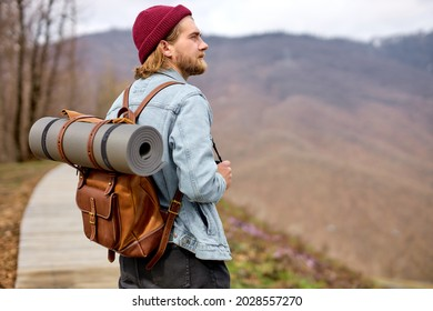 male traveler walking, going to explore wild environment at spring, side view on bearded guy with rucksack getting to mountain hills during hitch-hiking trip