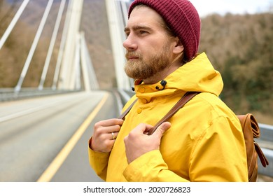 male traveler walking on asphalt road on bridge going to explore wild environment at spring, hipster guy with rucksack getting to mountain hills during hitch-hiking trip
