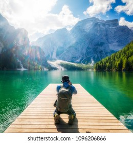 Male traveller taking photo of Lake Braies (Lago di Braies) in Dolomites Mountains, Italy. Hiking travel and adventure lifestyle.