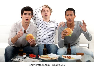 male trio watching soccer match on TV and eating hamburgers