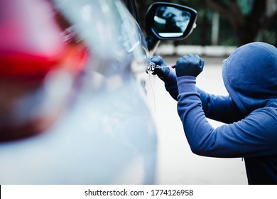 male trying tool to break into a car.