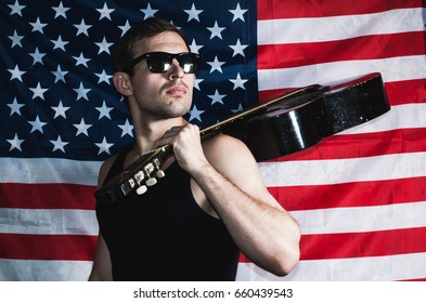 Male t-shirt with a guitar on the background of the American flag, guitarist with the sunglasses, rocker looks