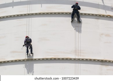 Male two worker rope access  inspection of thickness storage  white tank industry