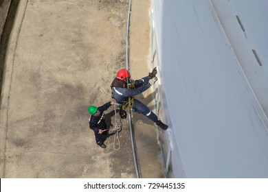 Male two worker rope access  inspection of thickness storage tank industry help catch the rope below.
